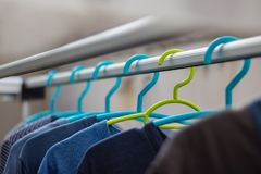 Green hanger Plastic In the clothes array with a blue hanger Plastic. stock photos
