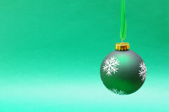 Green hanging bauble. Green Christmas bauble hanging on green organza ribbon, green background Stock Photography