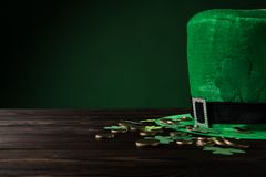 Green hat with golden coins and shamrock on wooden table Stock Photo