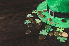Green hat with golden coins and shamrock on wooden table Royalty Free Stock Photography