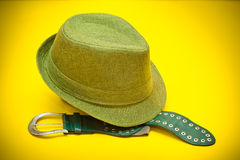 Green hat and a green belt with a buckle in western style. On an yellow background stock photography