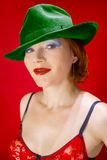 A green hat. Red-haired middle-aged woman dressed in a red bra and a green hat with a red background Royalty Free Stock Images