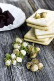 Green hazelnuts, biscuits and chocolate truffles. On wooden background Royalty Free Stock Photography