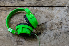 Green headphone on wooden table Stock Photo