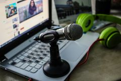 Green Headphones Near Laptop and Microphone Stock Photo