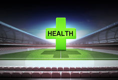 Green health cross in midfield of magic football stadium Royalty Free Stock Photography