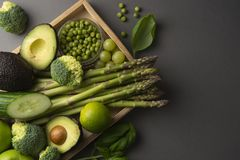 Green healthy food clean eating vegetables: asparagus, cucumber, basil, green peas, avocado, broccoli, lime, apples, grapes,. Green healthy food clean eating stock photo
