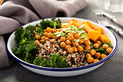 Green and healthy grain bowl with roasted chickpeas. Green and healthy vegan grain bowl with quinoa, butternut squash, kale and roasted chickpeas Stock Image
