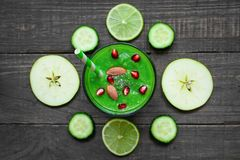 Green healthy smoothie in a glass chia seeds, pomegranate and nuts with a straw over rustic wooden table. top view stock image