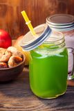 Green healthy smoothie in glass jar on rustik wood.  Royalty Free Stock Photography