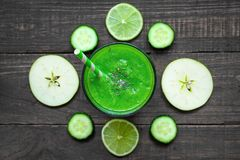 Green healthy smoothie in a glass with spinach, apple, cucumber and lime with a straw over rustic wooden table. top view. Detox drink stock photos