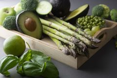 Green healthy vegetables: asparagus, cucumber, basil, green peas, avocado, broccoli, lime, apples, grapes, broccoli on dark. Green healthy vegetables asparagus royalty free stock photos