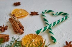 Green heart of candy cones with spices - anise stars, dried oranges, cinnamon sticks on the white background. Christmas candies stock images