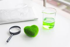 Green heart concept. Health Care researchs equipments. Green heart with a chemical organic test rube. Science glasses on laptop stock photography