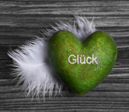 Green heart with german text for luck and a white feather on woo Royalty Free Stock Photography