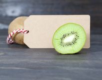 Green heart and halves of kiwi. Fruit with seeds, closeup, near the second kiwi is a paper tag for writing prices and so on stock images