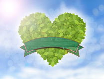 Green heart made of green leaves, symbol of eco friendly with green banner and blue sky Stock Image