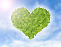 Green heart made of green leaves, symbol of eco friendly with green banner and blue sky Royalty Free Stock Image