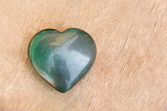 Green heart made of natural stone jade. A heart shaped stone lies on a brown or beige background. Love talisman, zen, spa.  stock images