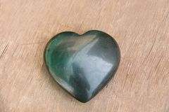 Green heart made of natural stone jade. A heart shaped stone lies on a brown or beige background. Love talisman, zen, spa.  stock photo