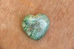 Green heart made of natural stone marble. A heart shaped stone lies on a brown or beige background. Love talisman, zen, spa.  royalty free stock photo