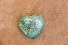 Green heart made of natural stone marble. A heart shaped stone lies on a brown or beige background. Love talisman, zen, spa.  royalty free stock image