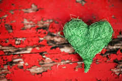 Green heart on red background Royalty Free Stock Image