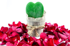 Green Heart, Red Roses. Green leaf heart surrounded by rose petals Royalty Free Stock Photography