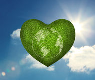 Green heart shape with earth drawn on it Royalty Free Stock Images