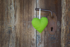 Green heart shape hanging on door handle - wooden background wit Stock Photography