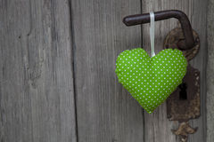 Green heart shape hanging on door handle - wooden background wit Royalty Free Stock Photography