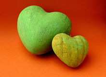 Green hearts. Two green hearts on orange background royalty free stock images