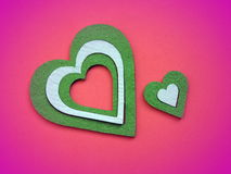 Green hearts on pink background stock photo