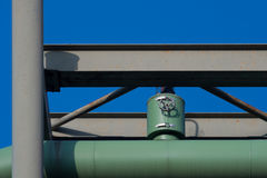 Green heat pipeline valve. Photo of green heat pipeline valve on gray construction with blue sky background - with clipping path Royalty Free Stock Photo