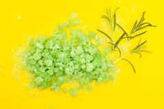 Green herbal bath salt with rosemary on a yellow background royalty free stock image
