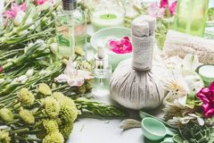Green herbal spa setting with massage balls, cosmetic products, herbs and flowers, front view. stock photography
