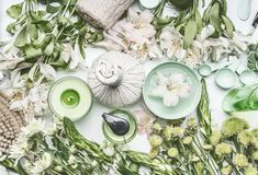 Green herbal spa setting with water bowl, flowers, candle, massage balls, cosmetic products, herbs and flowers, top view. Beauty, healthy lifestyle and stock photography