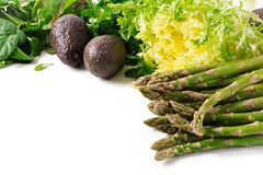 Green herbs, asparagus and black avocado on a white background. Top view. Flat lay stock image