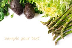 Green herbs, asparagus and black avocado on a white background. Top view. Flat lay stock images