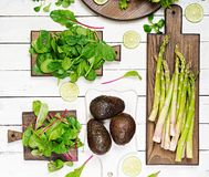 Green herbs, asparagus and black avocado on a white wooden background. Top view. Flat lay Royalty Free Stock Photo