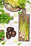 Green herbs, asparagus and black avocado on a white wooden background. Top view. Flat lay Royalty Free Stock Images