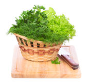 Green herbs in a basket on chopping board  on white Royalty Free Stock Photos