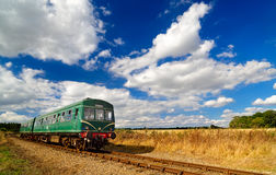 Green Heritage Railcar in Summer Countryside. A railcar from the 1950`s  in BR green with speed whiskers travels through pretty Norfolk farmland with striking Stock Photo