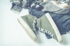 Green High-top Sneakers Beside Bottoms And Sunglasses Stock Image