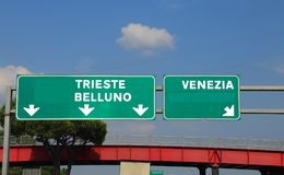 Green highway sign in Italy indicating the road to the cities. Green highway sign in Italy indicating the road to Venice Belluno and Trieste stock photography