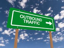 Outbound traffic highway sign. Green highway sign with white block text outbound traffic with white arrow against blue skies stock image