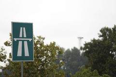 Green highway traffic sign. In front of trees in park stock images