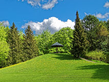 Green hill with bench under sun umbrella in park Royalty Free Stock Photos