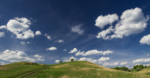 Green hill and a big blue sky with a few white clouds. Royalty Free Stock Photos