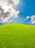 Green hill and bkue sky. With sun beam from clouds Stock Images